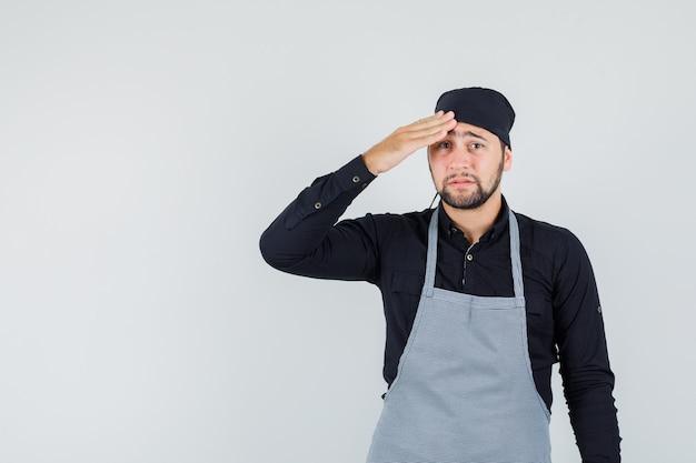 Hombre joven con la mano en la cabeza en camisa, delantal y mirando angustiado. vista frontal.