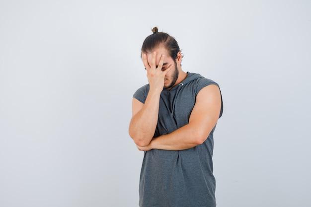 Hombre joven con la mano en la cara con capucha y mirando molesto, vista frontal.