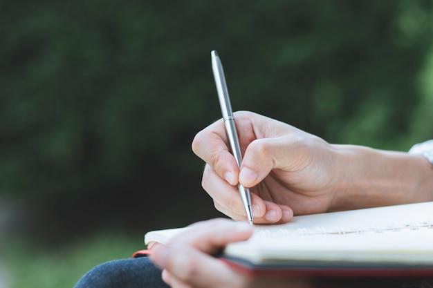 El hombre joven de la mano del cierre para arriba está sentado usando la pluma que escribe la libreta de la conferencia de la grabación en el libro en los parques.