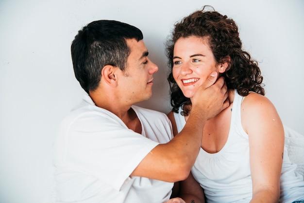 Hombre joven con la mano en el cuello feliz de la mujer