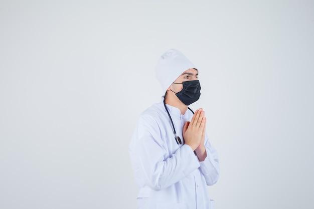 Hombre joven manteniendo las manos en gesto de oración en uniforme blanco, máscara y mirando esperanzado. vista frontal.