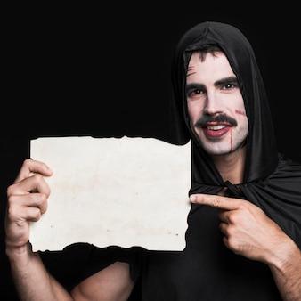 Hombre joven en manto negro y camiseta posando en estudio con un pedazo de papel en blanco