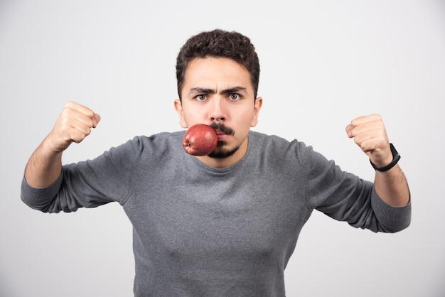 Hombre joven con manzana en la boca y listo para perforar.