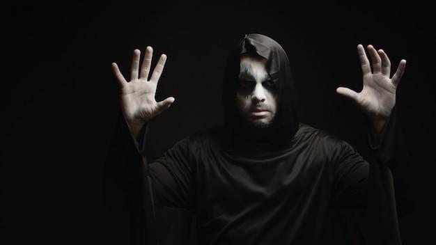 Hombre joven con maquillaje aterrador disfrazado de parca para halloween.