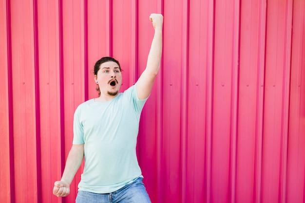 El hombre joven más divertido que aprieta su puño contra el contexto rosado del metal acanalado