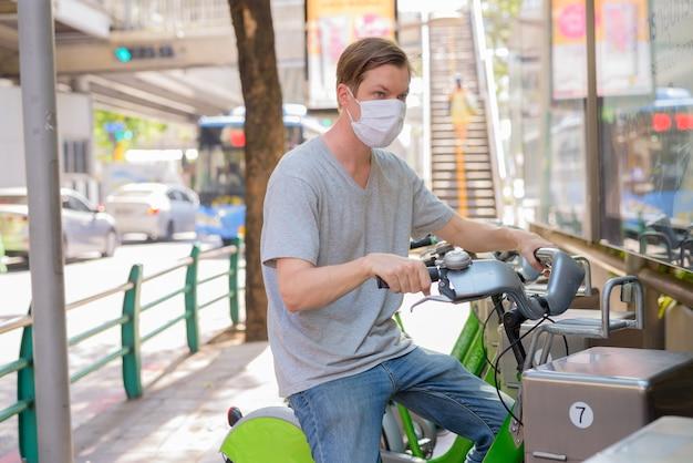 Hombre joven con máscara de alquiler de bicicletas en la estación de servicio de bicicletas públicas