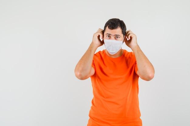 Hombre joven con máscara médica en camiseta naranja y mirando con cuidado, vista frontal.