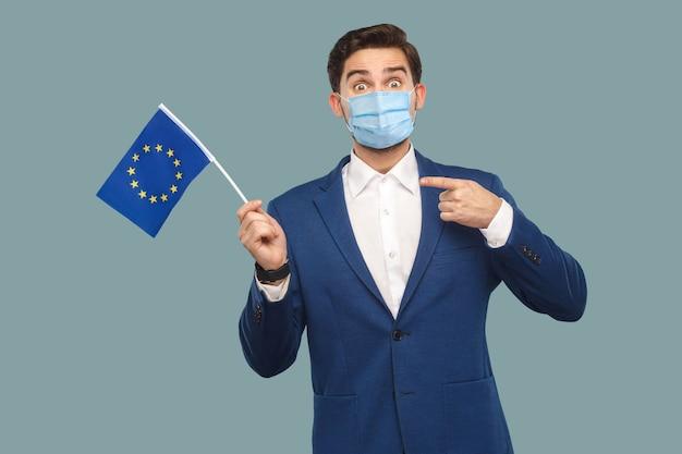 Hombre joven con máscara médica quirúrgica en chaqueta azul sosteniendo y apuntando a la bandera de la unión europea y mirando a cámara con ojos grandes y faee sorprendido. interior, tiro del estudio aislado sobre fondo azul.