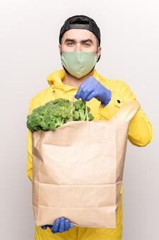 Hombre joven con máscara protectora y guantes sosteniendo una bolsa de papel con verduras frescas y pan mientras los entrega del supermercado