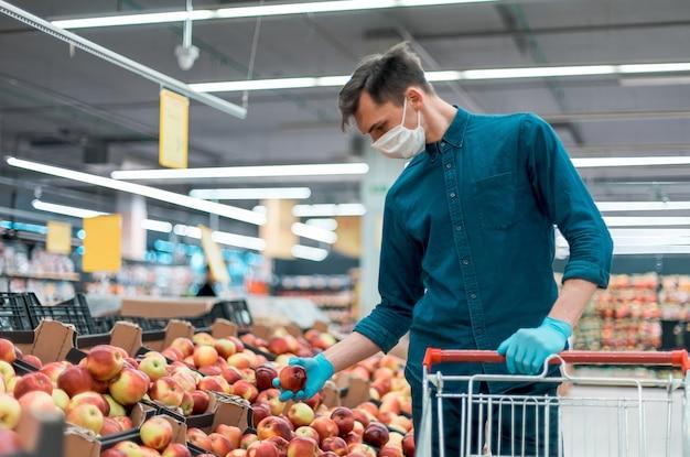Hombre joven con una máscara protectora de pie cerca del mostrador con manzanas. foto con copia del espacio