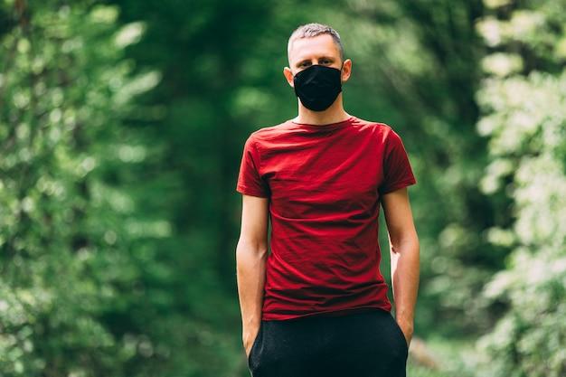 Hombre joven en mascarilla negra en el bosque. respiración de aire fresco durante una pandemia.