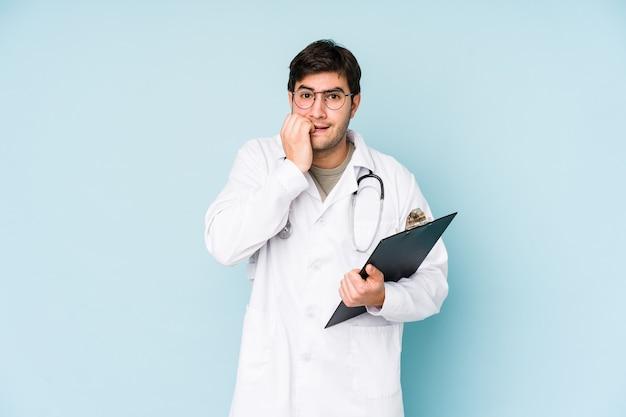 Hombre joven médico mordiéndose las uñas, nervioso y muy ansioso.