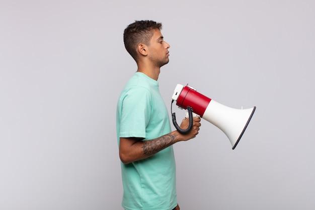 Hombre joven con un megáfono en la vista de perfil mirando para copiar el espacio por delante, pensando, imaginando o soñando despierto