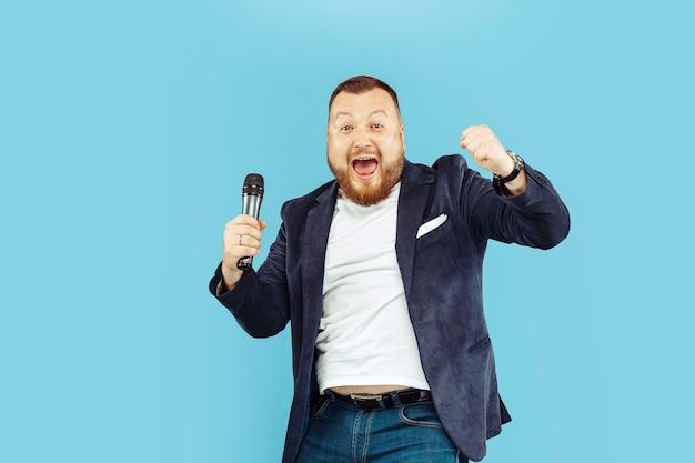 Hombre joven con micrófono en azul, concepto líder