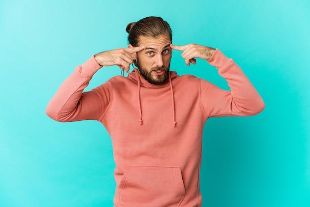 Hombre joven con mirada de cabello largo centrado en una tarea, manteniendo los dedos índices apuntando hacia la cabeza.