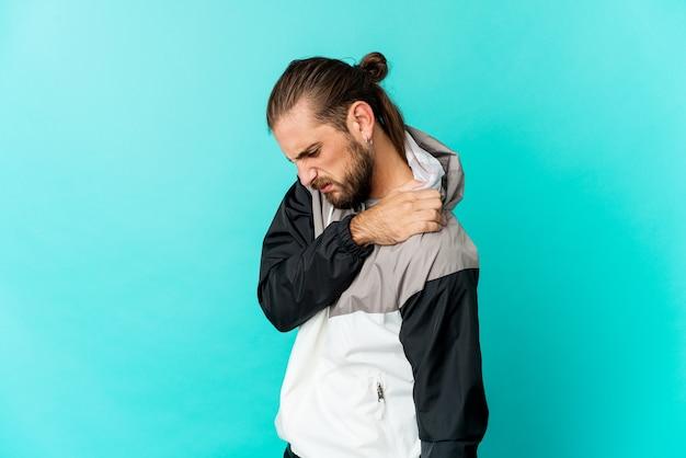 Hombre joven con mirada de pelo largo que tiene dolor de hombro.