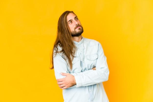Hombre joven con mirada de pelo largo soñando con lograr metas y propósitos