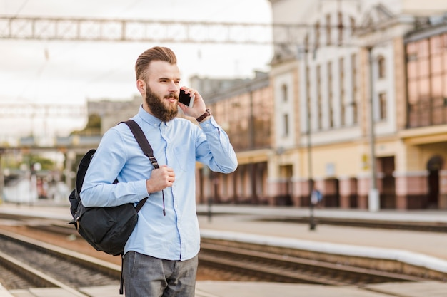 Hombre joven con mochila hablando por celular en la estación de tren