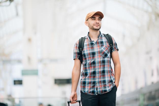 Hombre joven con mochila y maleta perdió el tren y esperando el próximo