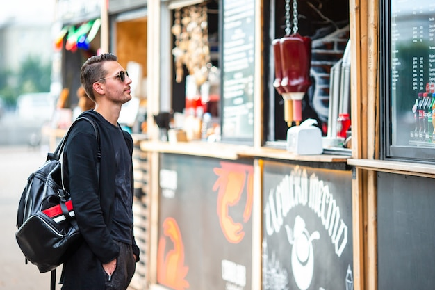 Hombre joven con mochila en el mercado de comida callejera al aire libre