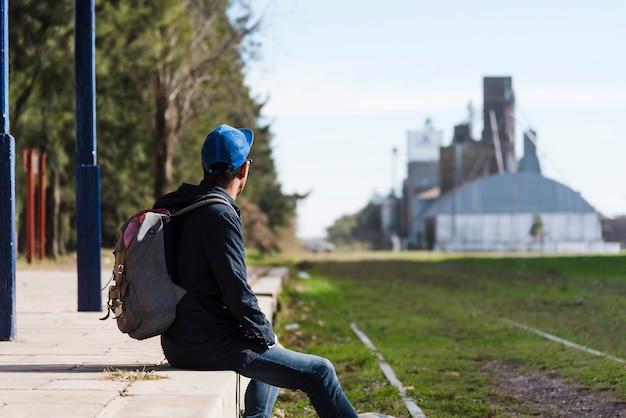 Hombre joven con mochila mirando a otro lado