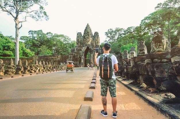 Hombre joven con mochila tomando foto de la entrada del templo de bayon angkor thom gate. siem reap, camboya