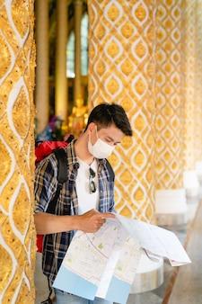 Hombre joven mochilero asiático en máscara facial de pie y comprobando la dirección en el mapa de papel en la mano en el hermoso templo tailandés