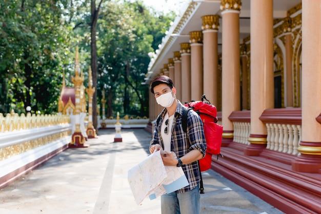 Hombre joven mochilero asiático en la mascarilla de pie y comprobando la dirección en el mapa de papel en la mano en el hermoso templo tailandés y punto en el mapa