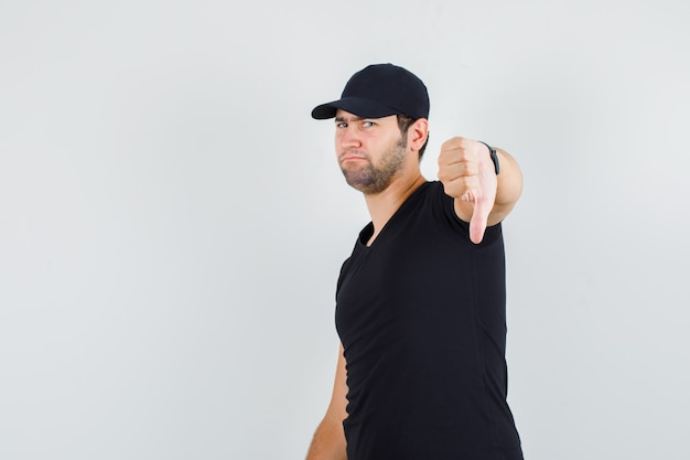 Hombre joven mostrando el pulgar hacia abajo en camiseta negra, gorra y mirando decepcionado