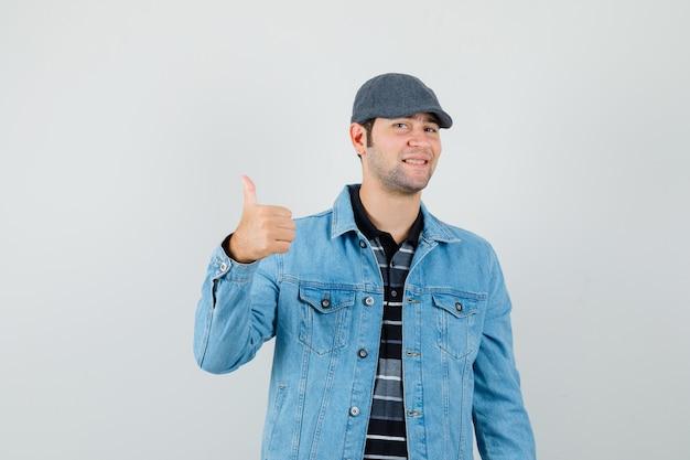 Hombre joven mostrando el pulgar hacia arriba en la chaqueta, gorra y mirando contento, vista frontal.
