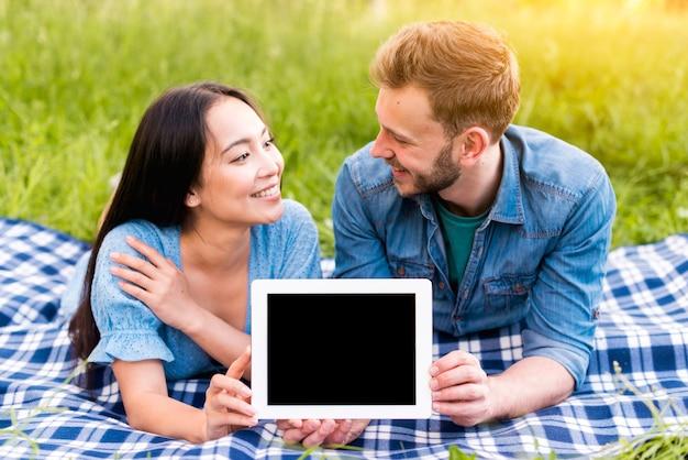 Hombre joven y mujer asiática mirándose y mostrando tableta