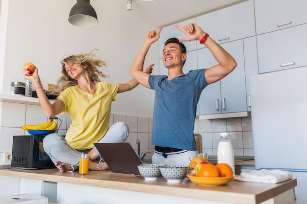 Hombre joven y mujer enamorada divirtiéndose saludable desayuno en la cocina por la mañana