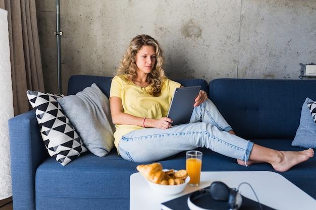 Hombre joven y mujer enamorada sentados en casa trabajando en línea