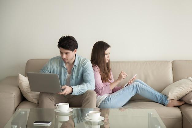 Hombre joven y mujer espalda con espalda usando laptop