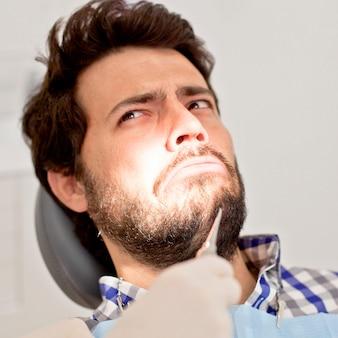 Hombre joven y mujer en un examen dental al dentista