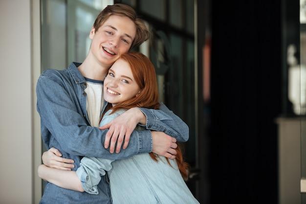 Hombre joven y mujer mirando la cámara mientras abrazaba