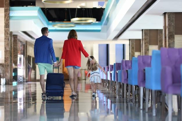 Hombre joven, mujer y niño con maleta van al vestíbulo del hotel