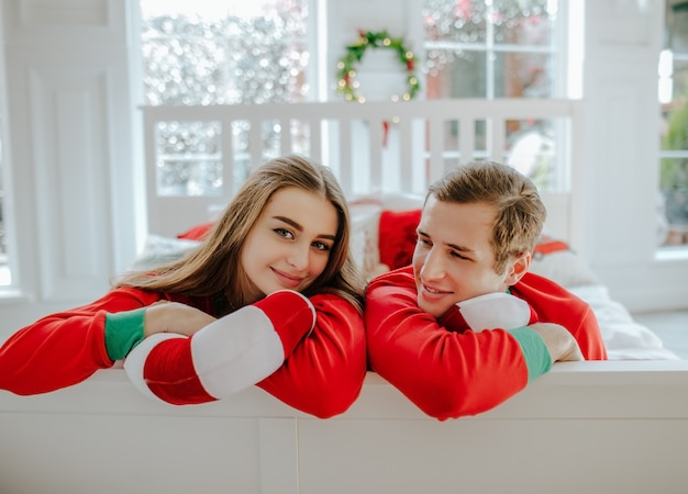 Hombre joven y mujer en pijama rojo de navidad acostado en una cama blanca en la habitación con ventana grande.