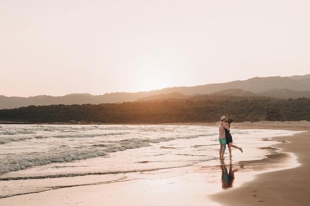 Hombre joven y mujer que se besan en la playa en la puesta del sol.