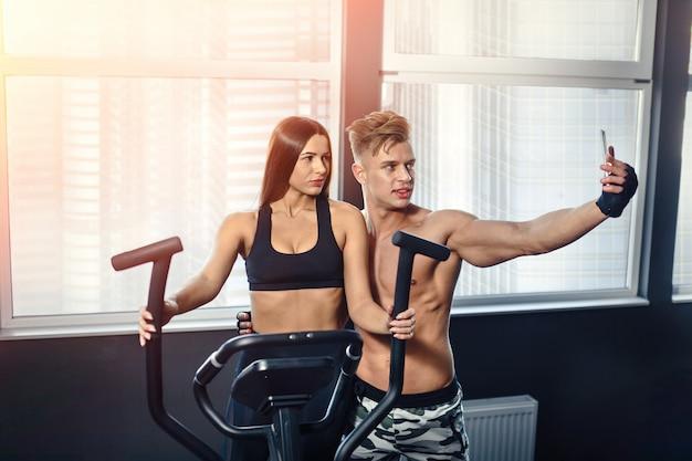 Hombre joven y mujer que toman autofotos en gimnasio, tecnología moderna, redes sociales