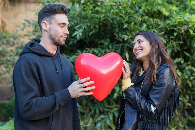 Hombre joven y mujer sonriente con globo en forma de corazón