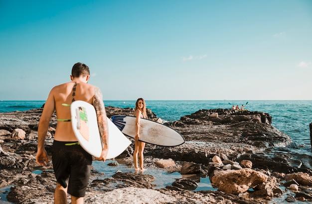 Hombre joven y mujer con tablas de surf en la orilla de piedra cerca del agua