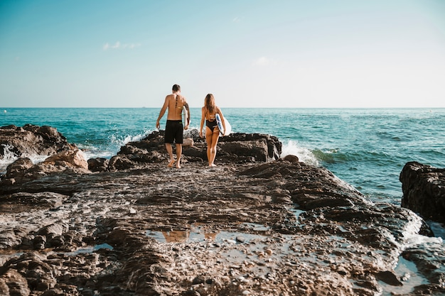 Hombre joven y mujer con tablas de surf que van en la orilla de piedra al agua