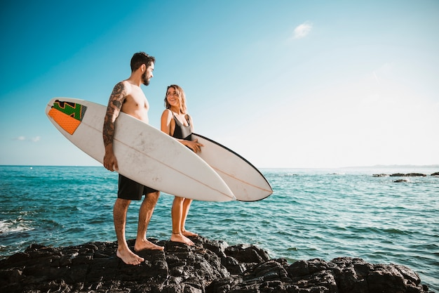 Hombre joven y mujer con tablas de surf en roca cerca del mar