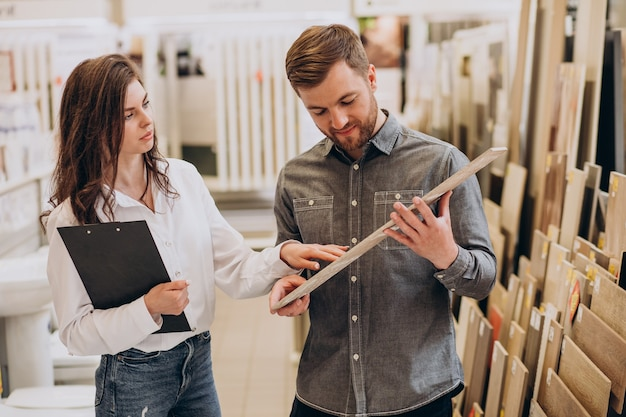 Hombre joven con mujer de ventas eligiendo azulejos en el mercado de la construcción