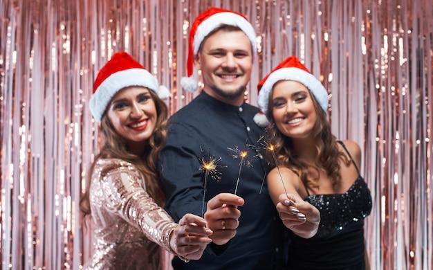 Hombre joven y mujeres disfrutando de navidad con bengalas en las manos.