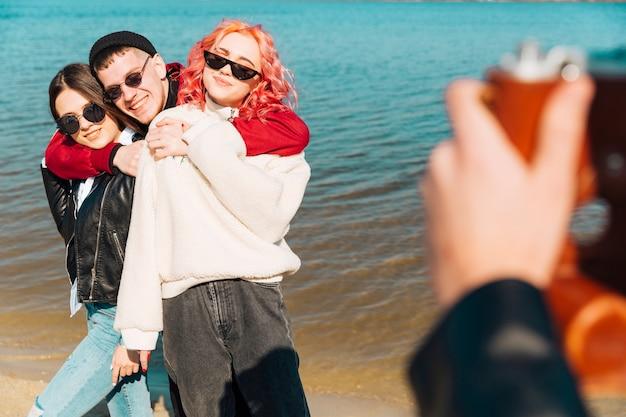 Hombre joven y mujeres posando para la foto en la orilla