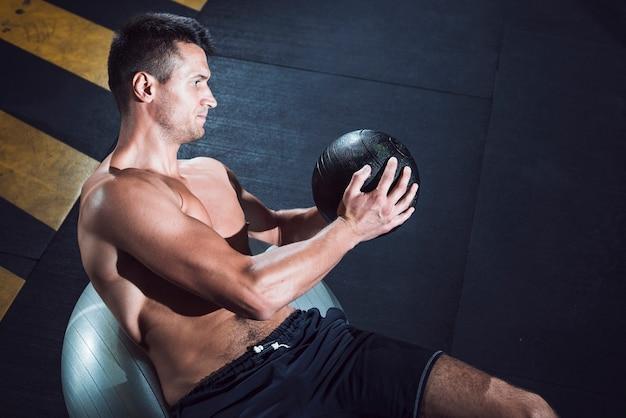 Hombre joven muscular que ejercita con la bola de medicina