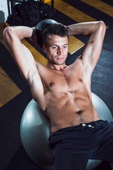 Hombre joven muscular que miente en bola de la aptitud