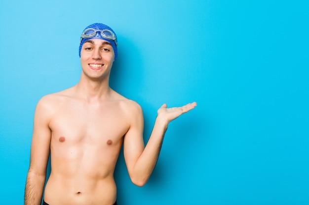 Hombre joven nadador mostrando un espacio de copia en una palma y sosteniendo otra mano en la cintura.